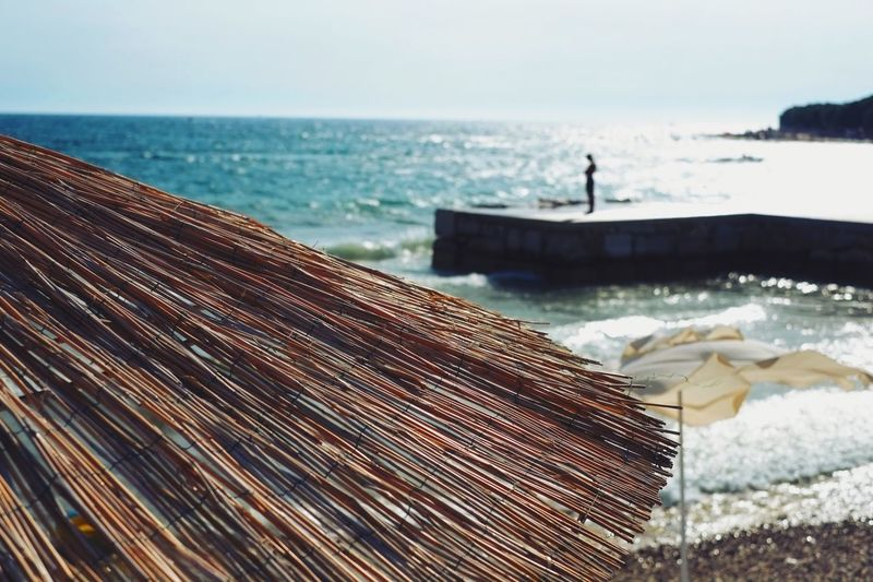 Close-Up Of Thatched Roof Against Beach