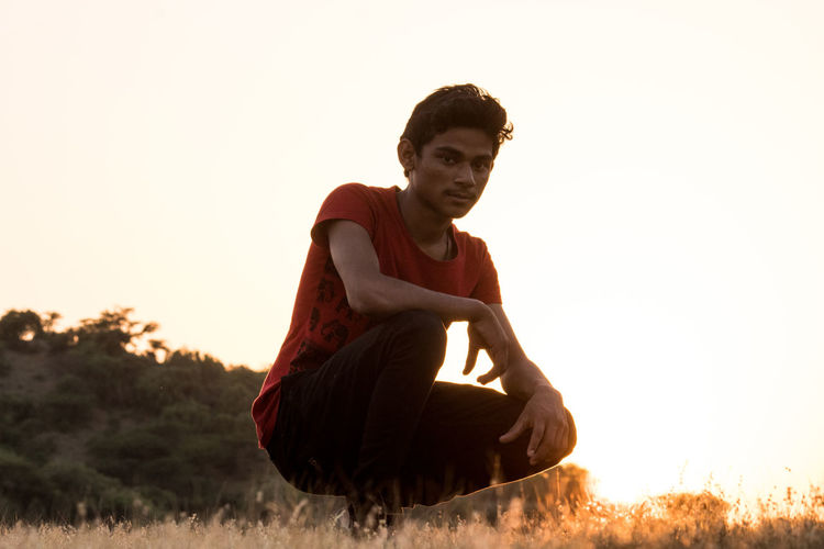 Full length of young man sitting on field against sky during sunset
