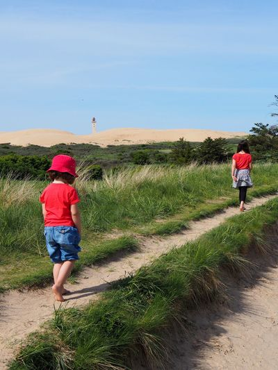 In May 2018 at Rubjerg Knude, Europe's biggest shifting sand dune, and the lighthouse Rubjerg Knude Fyr in the background. Rear View Real People Full Length Sky Grass Lifestyles Leisure Activity Plant Casual Clothing Men Nature Day People Walking Land Beauty In Nature Footpath Landscape Field Outdoors Shorts Sisters Girl Girls Children In Line Path Footpath barefoot Rubjerg Knude Rubjerg Knude Fyr Blue Sand Sand Dune Red Red Color Jeans