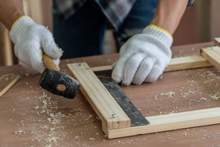 Close-up of man making wood on table