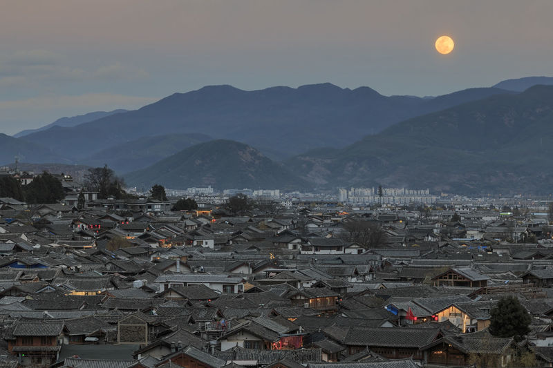 Rooftops in Lijiang old town and rising moon in the background, Yunnan Lijiang Old Town Rooftop Yunnan China Naxi Minority Unesco World Heritage Jade Dragon Snow Mountain Landscape Night Dusk