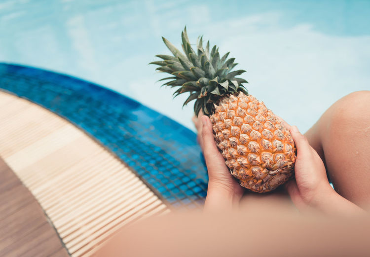 Summer concept, Close up portrait of woman is holding pineapple at poolside. Hand Human Hand Human Body Part One Person Holding Real People Food And Drink Body Part Food Unrecognizable Person Freshness Tropical Fruit Pineapple Lifestyles Day Focus On Foreground Healthy Eating Leisure Activity Finger Outdoors Swimming Swimming Pool Summer Holiday Vacations