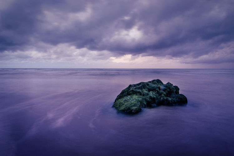 Rock formation at sea shore against cloudy sky during sunset
