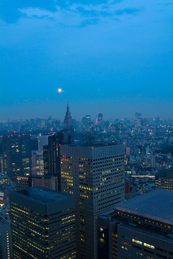 Illuminated cityscape against sky at dusk
