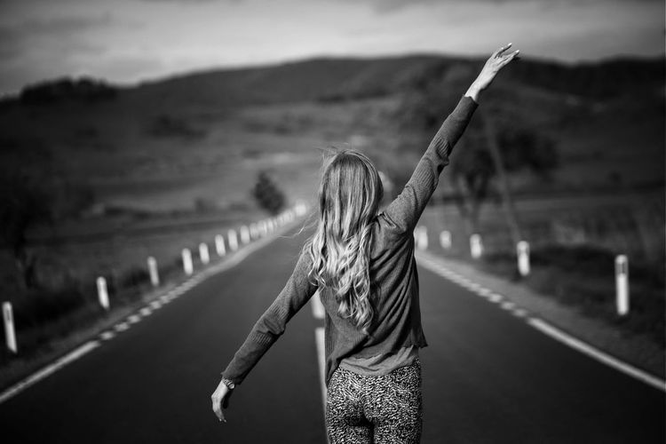 Rear View Of Woman With Arms Raised Standing On Country Road
