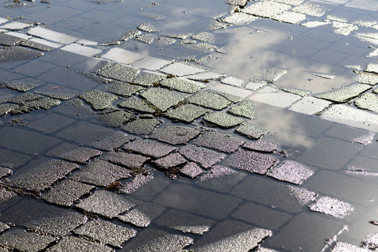 High angle view of puddle on cobblestone street during rainy season