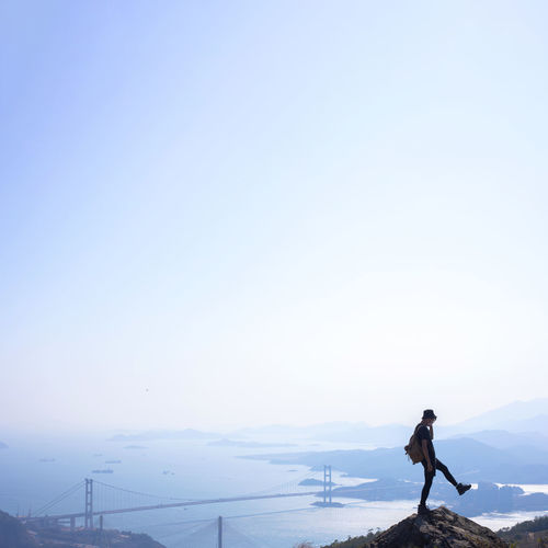 Man standing on mountain against clear sky during winter