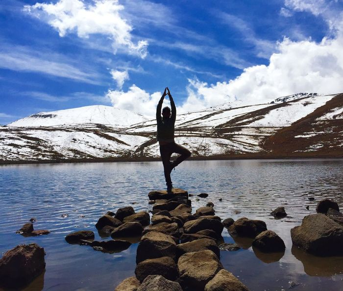Man doing yoga on rock in lake against sky