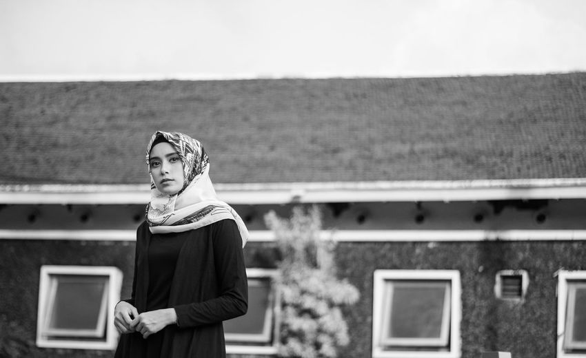 Young man in hijab standing against building