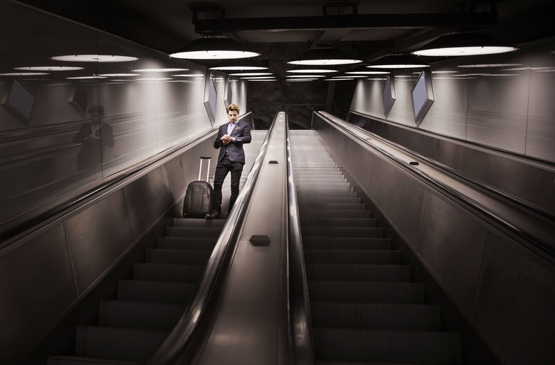 Rear view of man moving on escalator