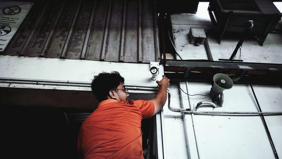Man repairing security camera