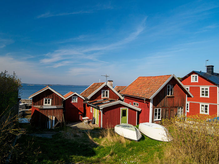Houses by buildings against blue sky