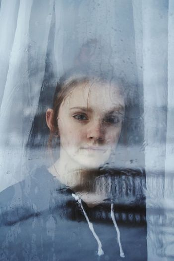 Close-Up Portrait Of Girl Looking Through Glass Window