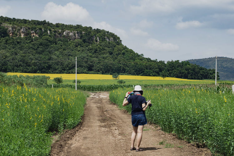Rear view of woman holding camera while standing on agricultural field against sky