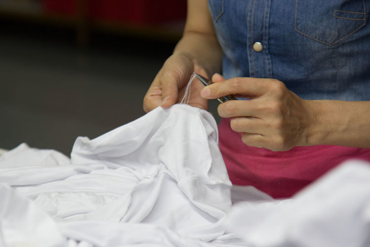 Midsection of woman stitching white textile