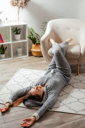 High angle view of young woman resting on floor at home