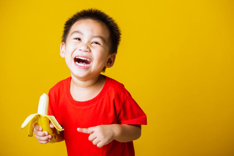 Smiling boy holding yellow against orange background