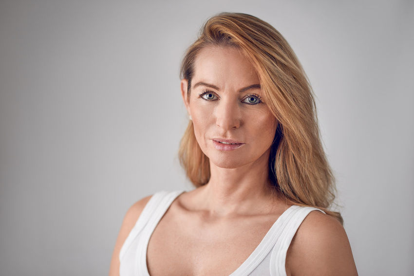 Attractive blond woman looking at the camera Adult Adults Only Beautiful People Beautiful Woman Beauty Best Ager Blond Hair Confidence  Gray Background Headshot Healthy Indoors  Looking At Camera Middle-aged One Person One Woman Only Portrait Skincare Studio Shot