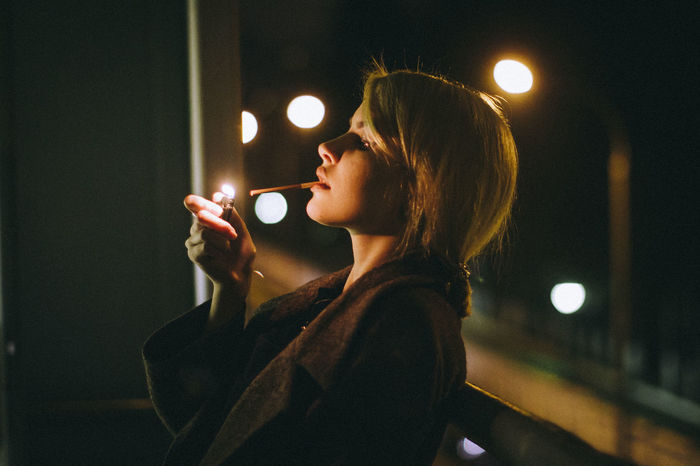 Woman smoking while standing against railing at night