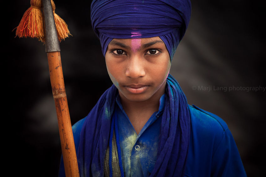 Portrait of a young Nihang Sikh at Hola Mohalla festival in Punjab, India. Black Background Blue Boy Close-up Color Portrait Documentary Eyes Face Focus On Foreground Front View Headshot India Indian Nihang Portrait Punjab Punjabi Sikh Sikhism Style Travel Turban Warrior Young Young Adult