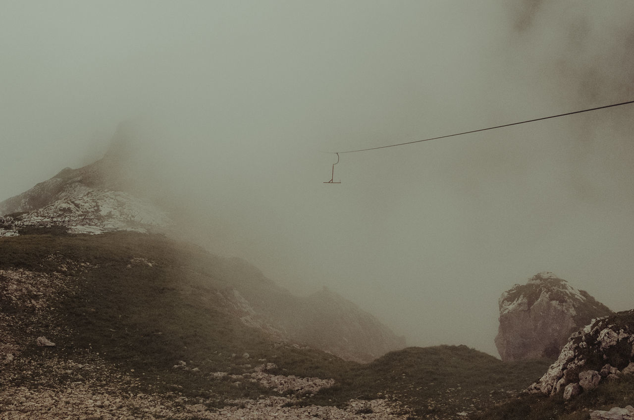 mountain, nature, weather, foggy, mountain range, fog, beauty in nature, cold temperature, scenics, outdoors, landscape, winter, tranquility, day, connection, sky, cable, tranquil scene, overhead cable car, physical geography, snow, mist, no people, snowcapped mountain, low angle view, technology, ski lift