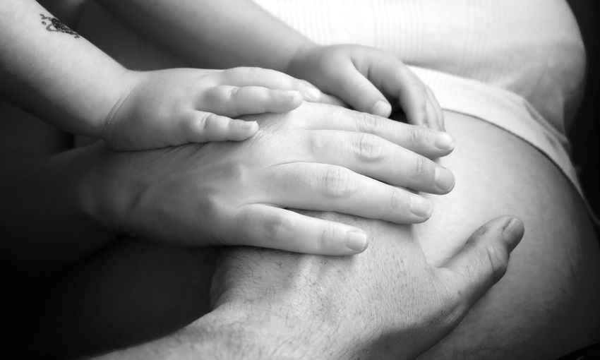 Cropped hands of man and daughter touching pregnant woman