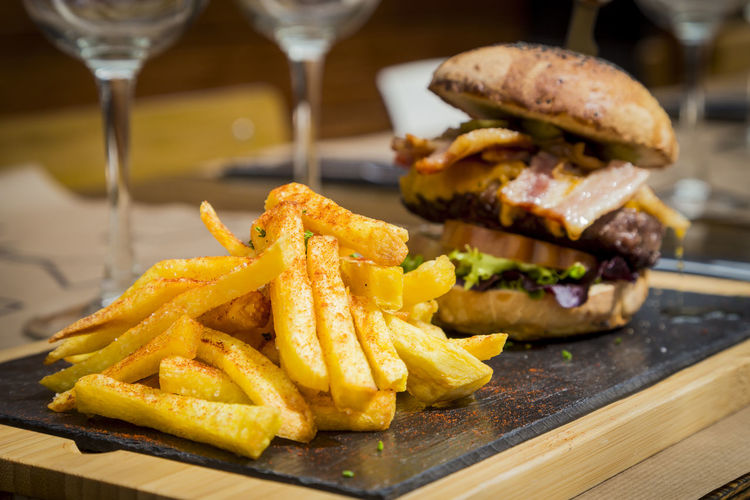Close-up of french fries and burger served on table