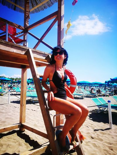 Full length of woman sitting on lifeguard chair at beach