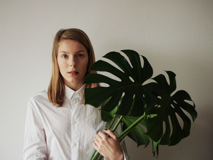 Portrait Of Young Woman Holding Leaf While Standing Against Wall