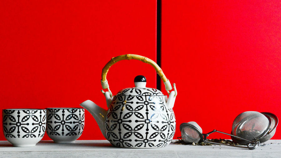 Close-up of crockery on table next to red wall