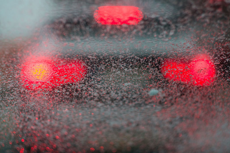 traffic congestion barely visible through driver rainy window Commuting Reflection Traffic Car City Close-up Condensation Congestion Glass Highway Illuminated Light Rain RainDrop Red Road Splattered Stop Texture Transparent Transportation Vehicle Water Wet Windshield