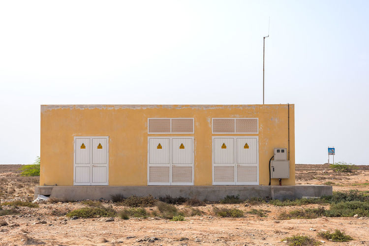 Electrical substation in Africa Ochre Substation Africa Architecture Arid Climate Building Exterior Built Structure Clear Sky Day Electrical Substation Field Grass No People Outdoors Sky Yellow
