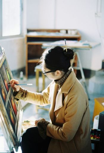 High angle view of artist painting on canvas
