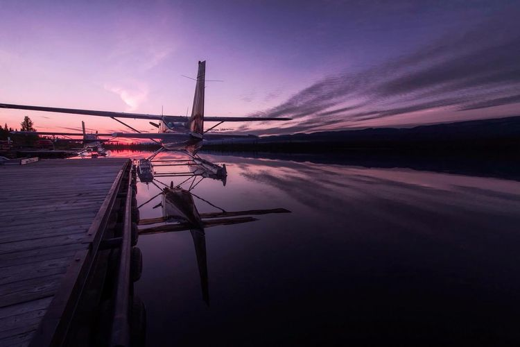 Air Vehicle By Pier Over Lake Against Sky During Sunset