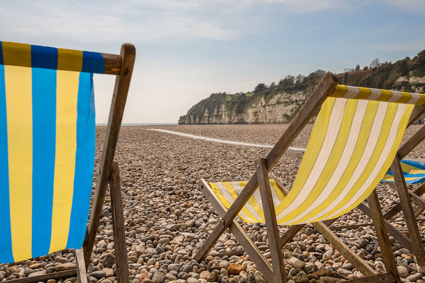 Empty tradition stripped canvas and wooden framed deck chairs on a pebble beach and chalk cliff backdrop, Beer, Devon, UK. Deck Chair Pebble Beach Beach Beach Chairs Beauty In Nature Chair Cloud - Sky Day Deck Chair Land Nature No People Outdoors Sand Scenics - Nature Sea Sky Striped Tranquil Scene Tranquility Water Yellow