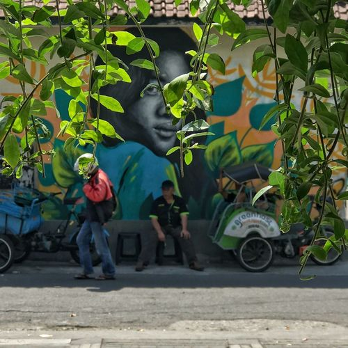 People on street amidst plants in city