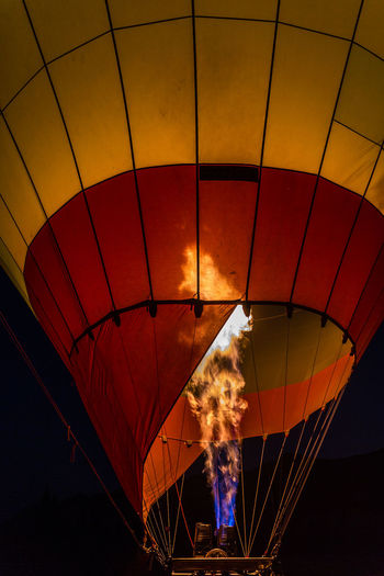 Fire inflating hot air balloon against sky at night