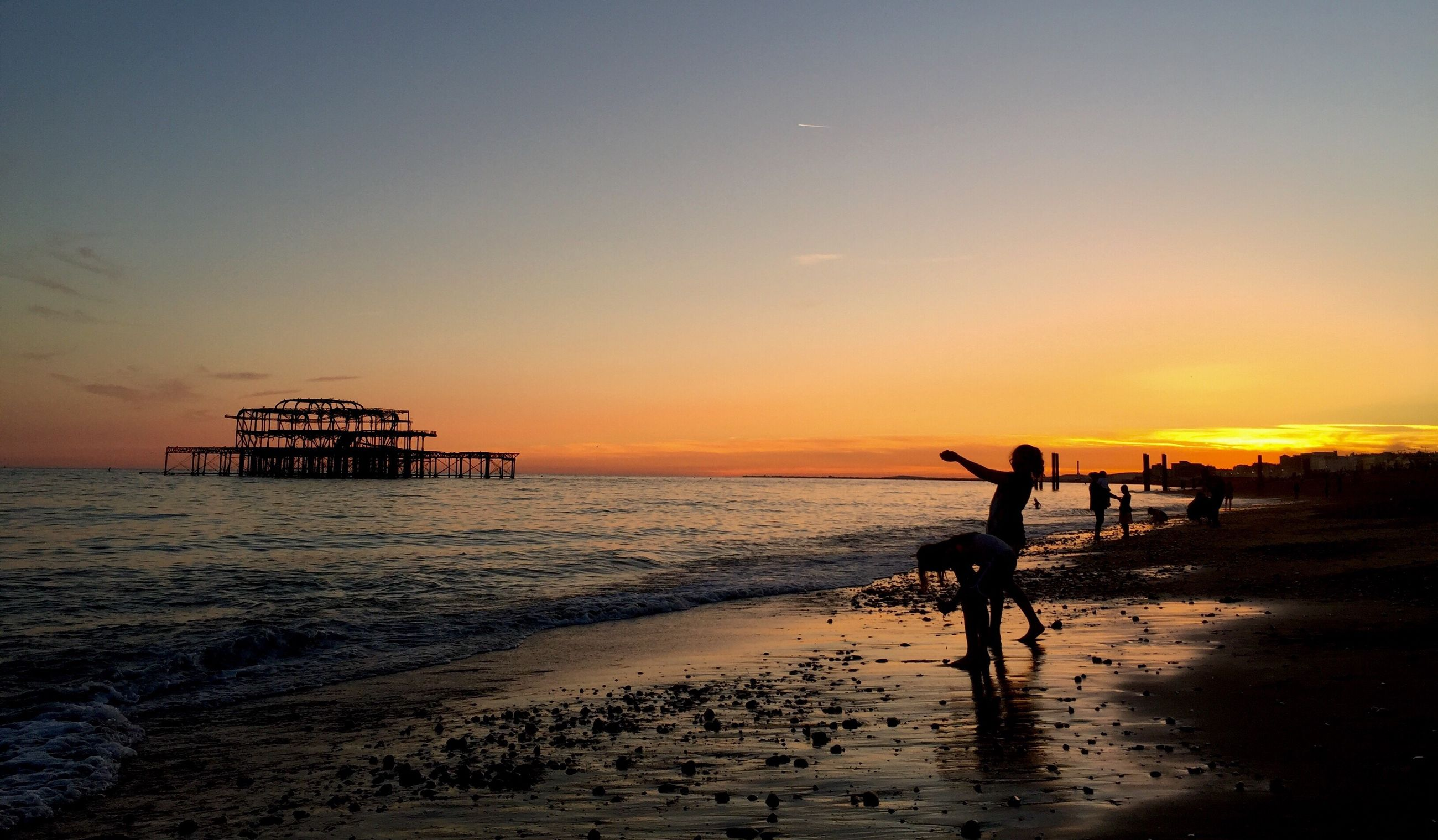 sea, beach, silhouette, water, sunset, horizon over water, scenics, shore, tranquil scene, tranquility, vacations, dusk, leisure activity, sky, togetherness, sand, beauty in nature, wave, full length, tourism, idyllic, nature, tourist, weekend activities, non-urban scene, orange color, outdoors