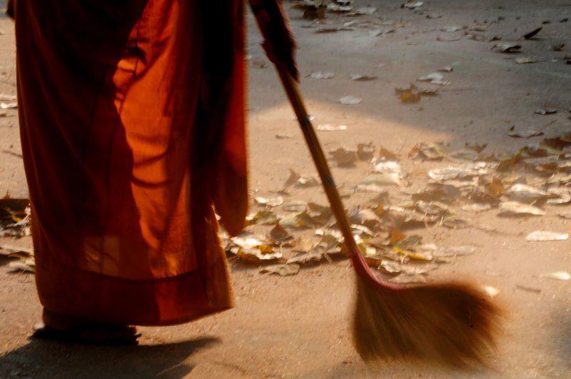 Adult Cleaning Day Human Hand Low Section Men Monk Thailand One Person Orange Robe Sweeping Outdoors People Real People Sand Shadow Standing Sunlight Sweeping M