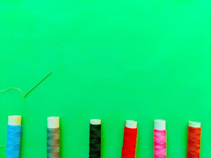 Close-up of multi colored pencils over green background