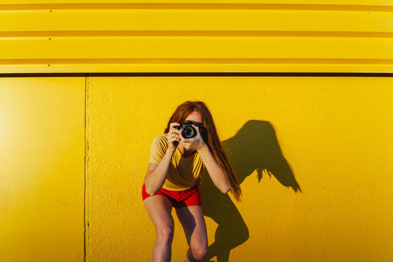 Portrait of young woman against yellow wall