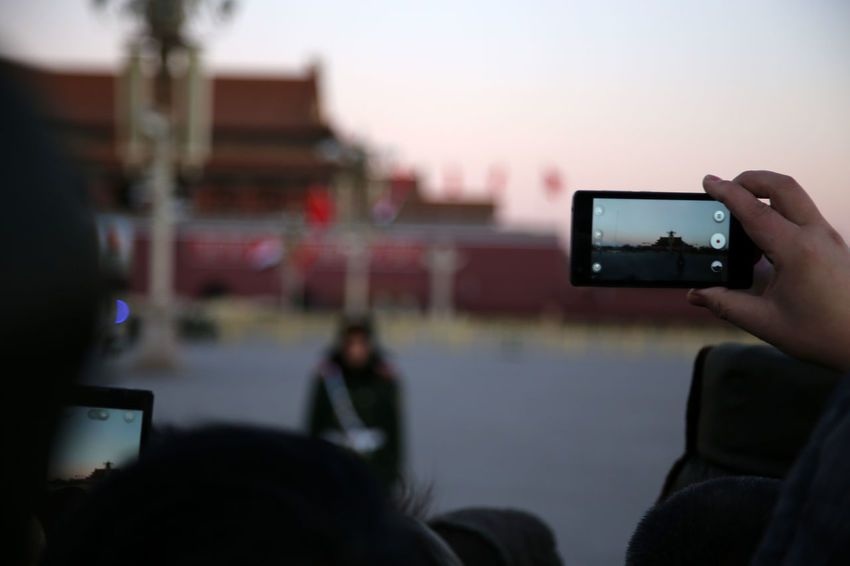 People filming the change of the Guards on Tian'anmen Square (Gate of Heavenly Peace) in Beijing, China at sunrise. Adult Change Of The Guards China Beauty Close-up Communication Device Screen Digital Camera Digital Viewfinder Filming Holding Horizontal Human Body Part Mobile Phone Over The Shoulder View Photo Messaging Photographing Photography Themes Portable Information Device Rear View Smart Phone Sunrise Silhouette Technology Tian'anmen Square Tiananmen Square Wireless Technology