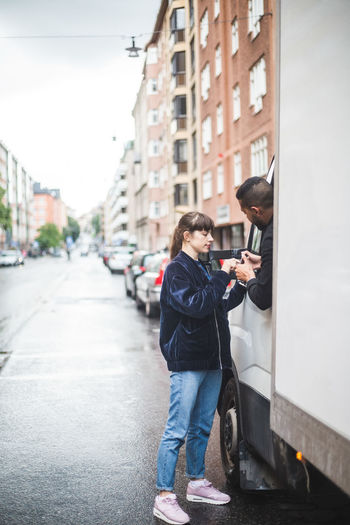 Man photographing woman using mobile phone in city