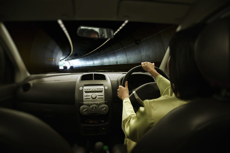 Rear view of woman driving car in tunnel