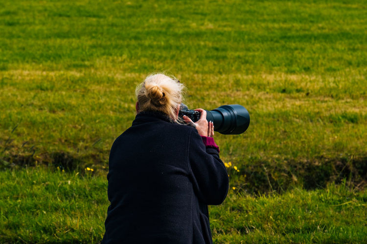 Rear view of woman photographing with camera while standing on grassy field