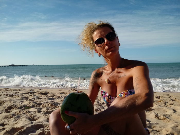 Woman Wearing Sunglasses While Sitting With Coconut On Sand At Beach Against Sky