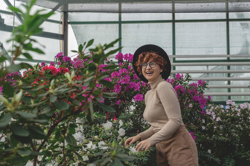 A beautiful plus size girl in a hat laughs among the green plants of the greenhouse.