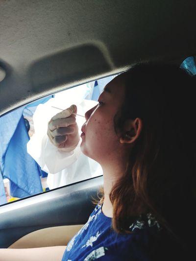 Portrait of girl in car taking antigen swab test for covid-19 detection