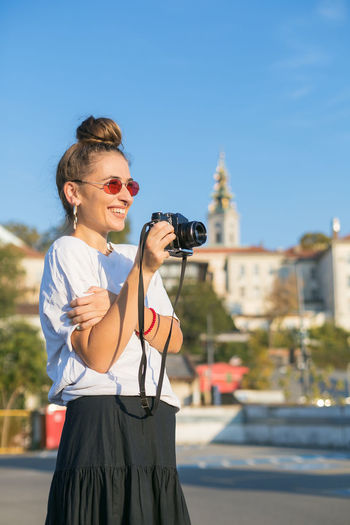 Woman photographing with camera against sky in city