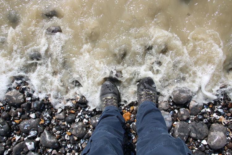 Beach Boots Close-up Day Human Leg Low Section One Person Outdoors Pebbles And Stones People Real People Splashing Standing Tide Walking Boots Water Waves